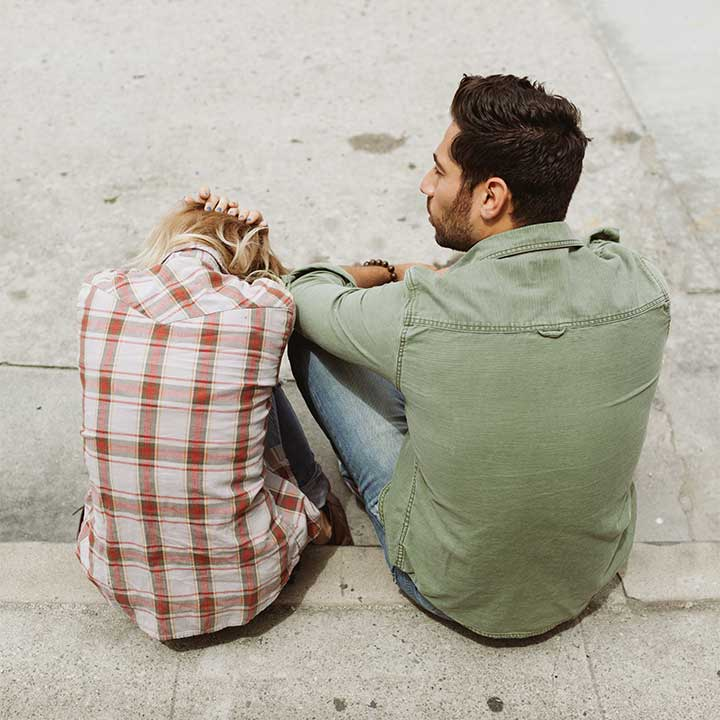Couple sitting on pavement, head in hands